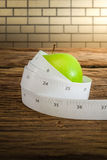 Cinta de medición envuelta alrededor de una manzana verde Imagenes de archivo