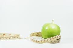 Cinta de medición envuelta alrededor de una manzana verde Fotografía de archivo