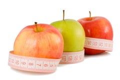Cinta de medición rosada y tres manzanas Foto de archivo libre de regalías
