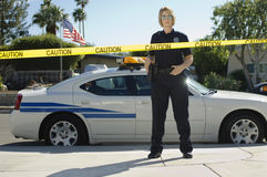 Cinta de Standing Behind Caution del oficial de policía fotografía de archivo libre de regalías