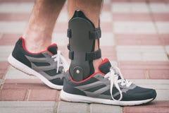 Cinta de tornozelo vestindo do homem foto de stock