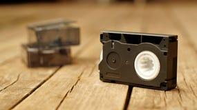 Cinta de vídeo compacta vieja en el piso de madera fotos de archivo