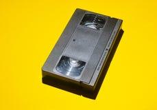 Cinta de vídeo retra de 80s en un fondo amarillo Medias tecnologías obsoletas Fotos de archivo