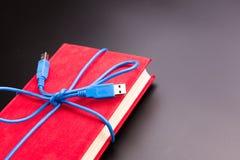 Cinta del cable del usb en el libro Imagen de archivo