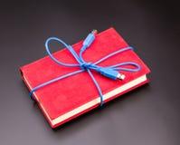 Cinta del cable del usb en el libro como presente Fotos de archivo