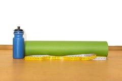 Cinta del centímetro, estera de la yoga y botella de agua para el ejercicio en fondo amarillo Imagen de archivo