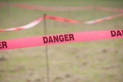 Cinta del límite del peligro en un campo. Foto de archivo
