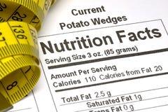 Cinta métrica al lado de hechos de la nutrición imagenes de archivo
