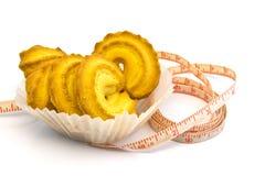Cinta métrica alrededor de las galletas aisladas en blanco Imagen de archivo