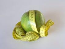 Cinta métrica amarilla envuelta alrededor de una manzana verde deliciosa Foto de archivo