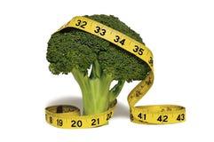 Cinta métrica amarilla sobre un tallo del bróculi Imagen de archivo libre de regalías