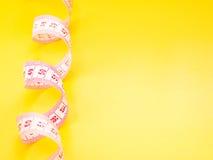 Cinta métrica blanca en fondo amarillo Fotos de archivo libres de regalías