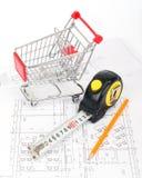Cinta métrica con el lápiz y el carro de la compra Foto de archivo libre de regalías