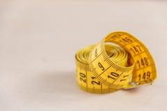 Cinta métrica curvada Opinión del primer la cinta métrica amarilla Foto de archivo libre de regalías