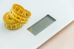 Cinta métrica curvada Opinión del primer la cinta métrica amarilla en el pesador Imagen de archivo libre de regalías