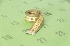 Cinta métrica en un calendario Fotos de archivo