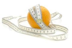 Cinta métrica envuelta alrededor de naranja Imagenes de archivo