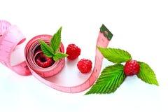 Cinta métrica envuelta alrededor de una frambuesa/de un concepto maduros de la salud, dieta Imagenes de archivo