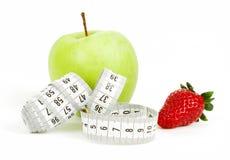 Cinta métrica envuelta alrededor de una manzana y de una fresa verdes como símbolo de la dieta Imagen de archivo
