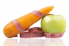 Cinta métrica envuelta alrededor de una manzana y de una zanahoria verdes Fotografía de archivo