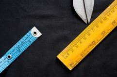 Cinta métrica, escala y tijeras en el paño negro imagen de archivo