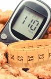 Cinta métrica, metro de la glucosa con las galletas del nivel y de harina de avena del azúcar del resultado, diabetes y concepto  Foto de archivo