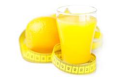 Cinta métrica, naranja y un vidrio de zumo de naranja Imagen de archivo libre de regalías