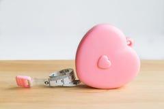 Cinta métrica rosada del corazón en la madera foto de archivo