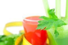 Cinta métrica, vidrio de jugo del apio y vidrio de jugo de zanahoria Foto de archivo libre de regalías