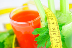 Cinta métrica, vidrio de jugo del apio y vidrio de jugo de zanahoria Imagenes de archivo