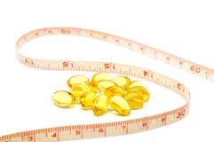 Cinta métrica y cápsulas para el concepto de dieta Imagen de archivo libre de regalías