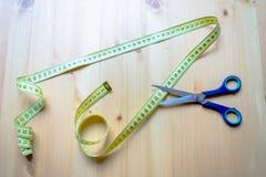 Cinta métrica y tijeras que mienten en una tabla de madera foto de archivo libre de regalías