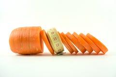 Cinta métrica y zanahorias cortadas Fotos de archivo