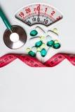 Cinta métrica del estetoscopio de las píldoras en escalas Cuidado médico Fotografía de archivo libre de regalías