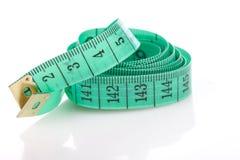 Cinta métrica verde, símbolo de la exactitud, en blanco Fotografía de archivo libre de regalías