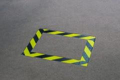 Cinta negra y amarilla colocada en la alfombra para evitar cualquier accidente Foto de archivo