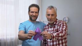 Cinta púrpura de la demostración masculina voluntaria y mayor, conciencia de la enfermedad de Alzheimer almacen de metraje de vídeo