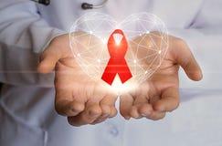 Cinta para la lucha contra símbolo SIDA y del corazón en las manos fotos de archivo