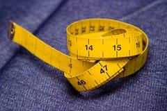 Cinta que mide en pantalones vaqueros Fotografía de archivo libre de regalías
