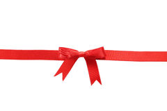 Cinta roja con el arco en el fondo blanco Foto de archivo libre de regalías