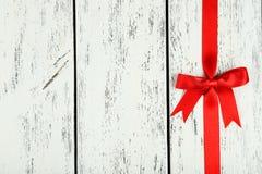 Cinta roja con el arco en el fondo de madera blanco Foto de archivo libre de regalías