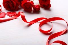 Cinta roja con las rosas y los corazones en la tabla Imágenes de archivo libres de regalías