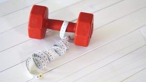 Cinta roja de la pesa de gimnasia y del centímetro de la aptitud en la tabla de madera blanca metrajes