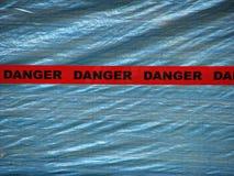 Cinta roja del peligro sobre un fondo azul de la pared Foto de archivo