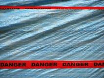 Cinta roja del peligro sobre un fondo azul de la pared Imágenes de archivo libres de regalías