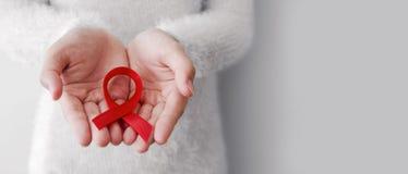 Cinta roja en las manos de la mujer para el Día Mundial del Sida Imagenes de archivo