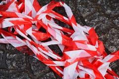 Cinta roja y blanca de la barrera en una pila en la tierra Foto de archivo libre de regalías