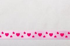Cinta rosada del corazón en fondo del paño Imagenes de archivo