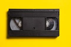 Cinta video cl?sica negra en un fondo amarillo fotografía de archivo