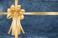 Cinta y arco de oro, abrigo en fondo azul de caja de regalo de la textura de los vaqueros del dril de algodón imagenes de archivo